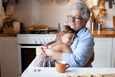 Senior woman hugging child at home. Happy family enjoying kindness, support, care together in cozy kitchen. Cute girl visiting grandmother. Lifestyle moments. Holiday Thanksgiving.